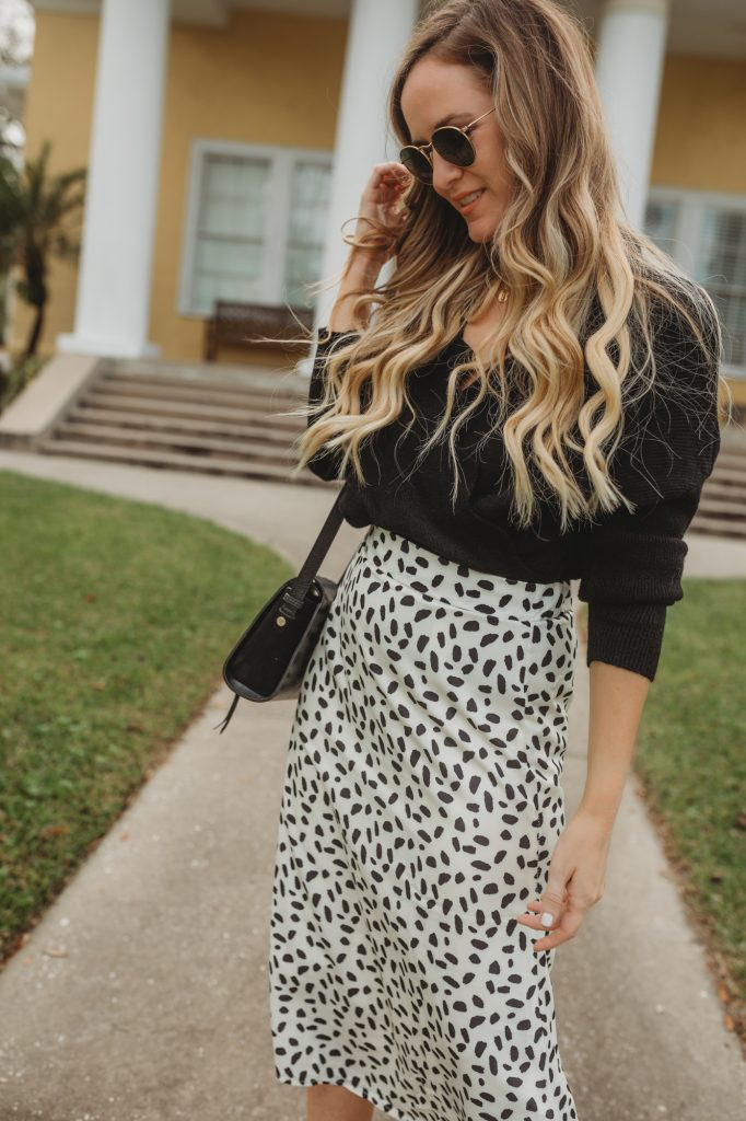 Shannon Jenkins of Upbeat Soles styles a fall black and white outfit with spotted midi skirt, black cropped sweat, and black ankle booties