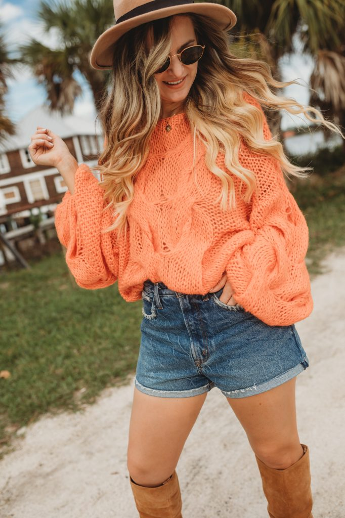 Shannon Jenkins of Upbeat Soles styles a boho fall outfit with Sam Edelman western suede boots, Chicwish oversized sweater, and Abercrombie shorts