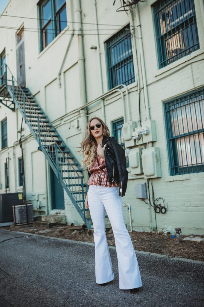 Shannon Jenkins of Upbeat Soles styles an edgy holiday outfit with sequin peplum Adelyn Rae top, Lee flares jeans, and BlankNYC leather jacket