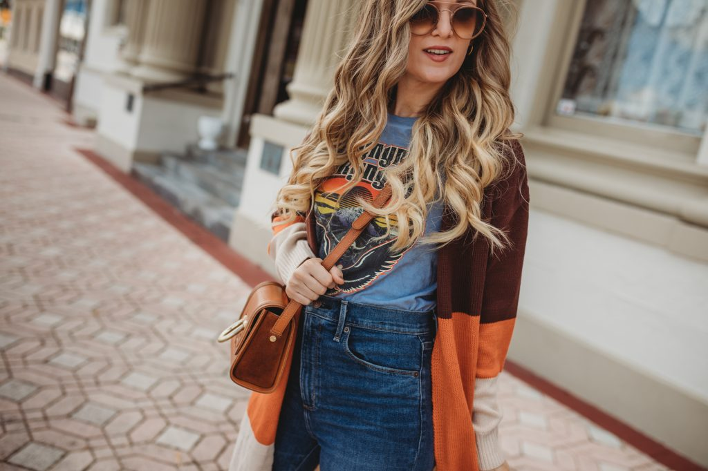 Shannon Jenkins of Upbeat Soles styles a boho fall outfit with color block cardigan, band tee, high waisted flare jeans and round Ray Ban sunglasses
