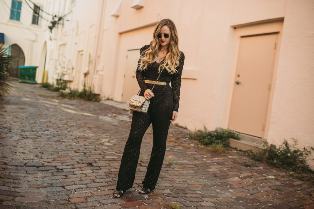 Shannon Jenkins of Upbeat Soles styles a new years eve outfit with sequin jumpsuit, Aimee Kestenberg metallic crossbody bag, and Ray Ban sunglasses