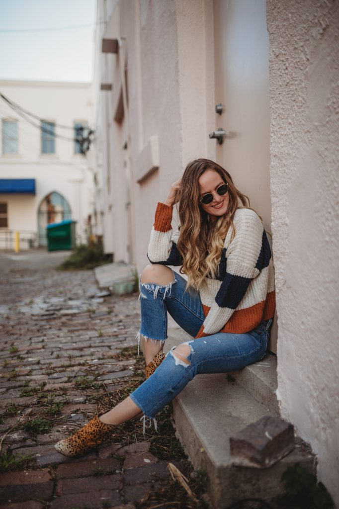 Shannon Jenkins of Upbeat Soles styles a casual weekend winter outfit with cropped striped sweater, distressed Levi's, and leopard booties