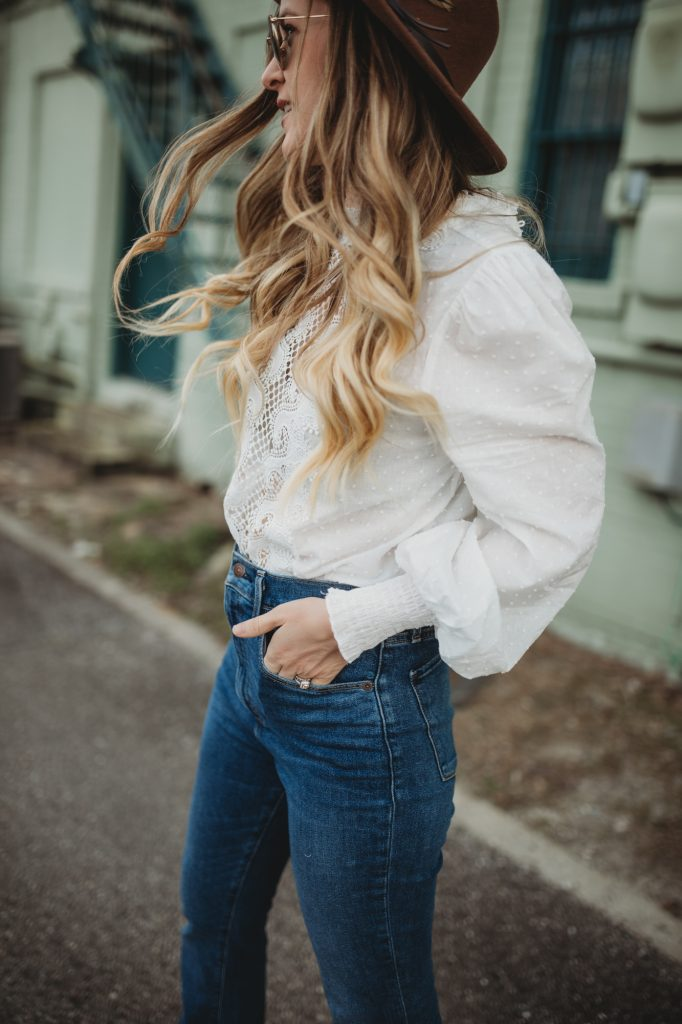 Shannon Jenkins of Upbeat Soles styles a boho date night outfit with lace balloon sleeve top, Abercrombie flared jeans and round Ray Ban sunglasses