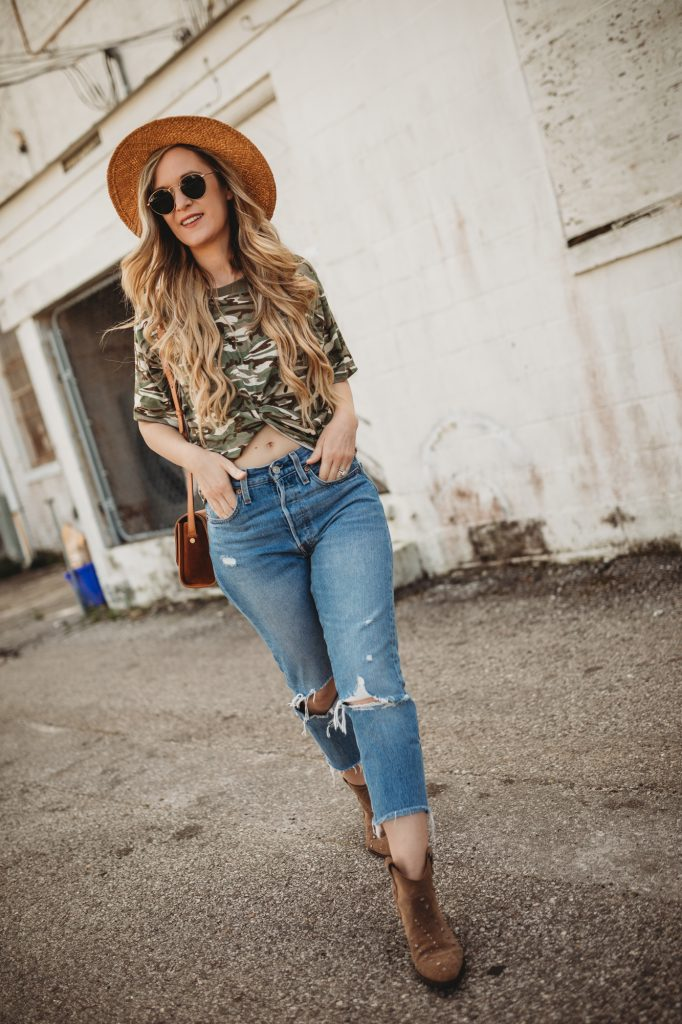 Shannon Jenkins of Upbeat Soles styles a cute spring transition outfit with knotted camo shirt, Levi's wedgie jeans, and suede Sam Edelman booties