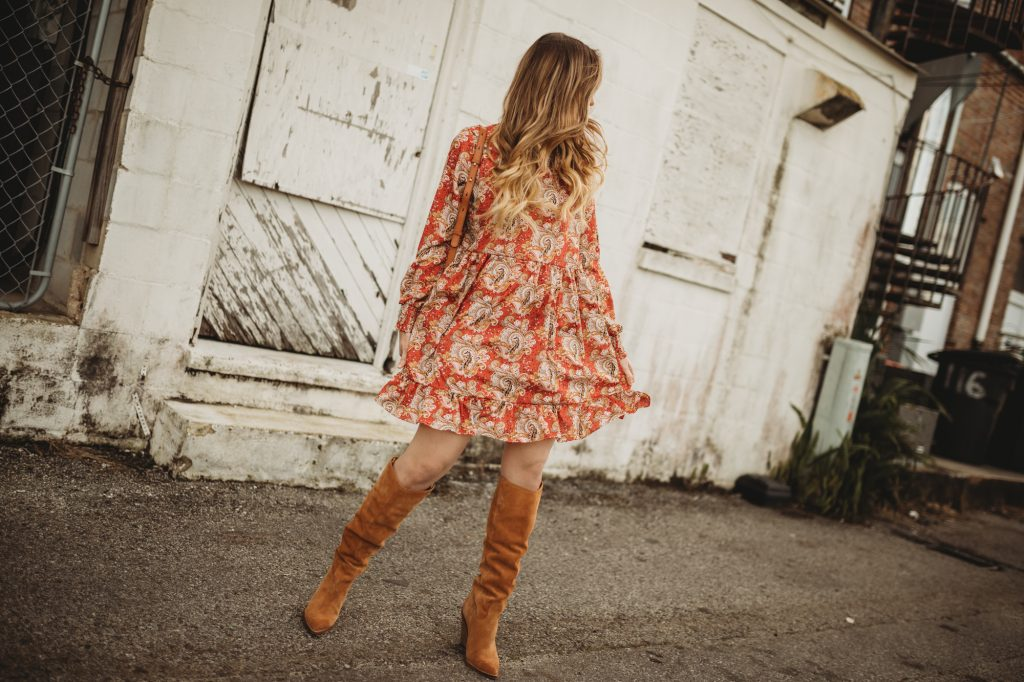 Shannon Jenkins of Upbeat Soles styles a cute boho winter outfit with paisley boho dress, slouchy suede boots, and Ray Ban Icon sunglasses