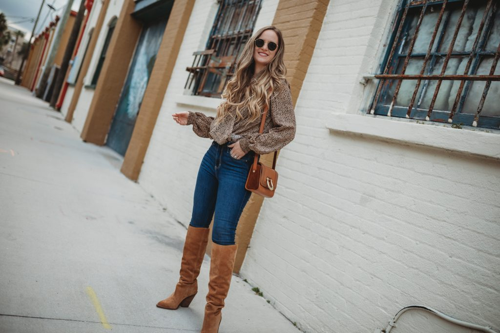 Shannon Jenkins of Upbeat Soles styles an easy winter weekend outfit with leopard wrap top, high waisted jeans, and Sam Edelman suede slouchy boots