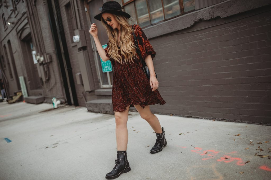 Shannon Jenkins of Upbeat Soles styles a spring transition outfit with a dark floral boho dress, Sam Edelman studded combat boots, and round Ray Bans