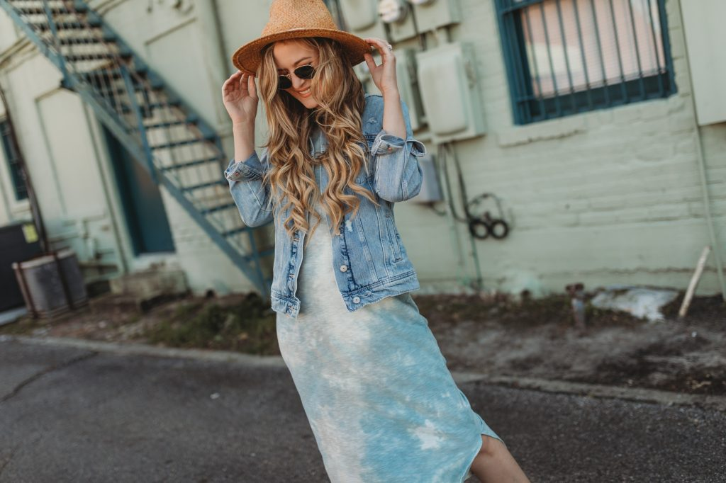Shannon Jenkins of Upbeat Soles styles a cute spring outfit with a tie dye midi dress from Target, Old Navy denim jacket, and cream Van sneakers