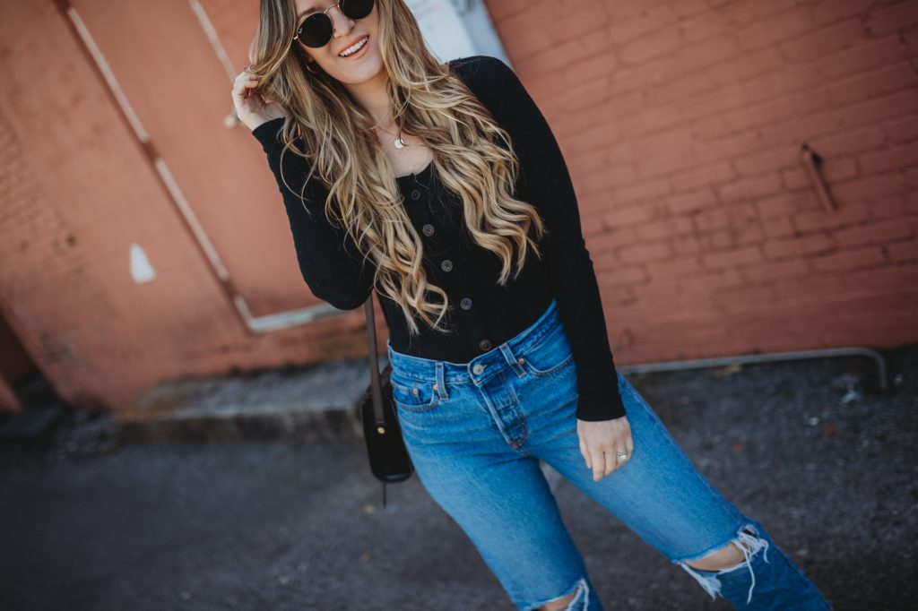 Shannon Jenkins of Upbeat Soles styles an edgy spring transition outfit with Abercrombie sweater, Levi's wedgie jeans, and leopard Michael Kors boots