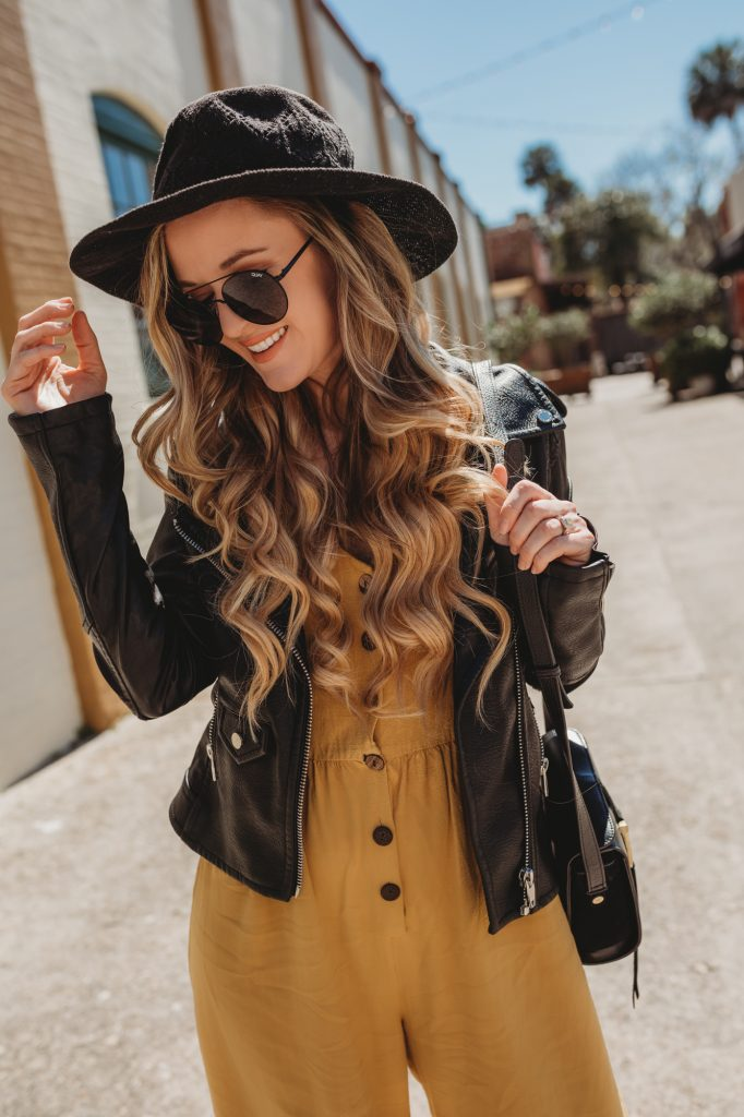 Shannon Jenkins of Upbeat Soles styles a cute spring transition outfit with mustard jumpsuit, Blank NYC leather jacket, and black booties