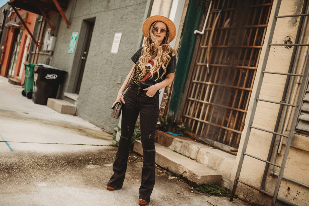 Shannon Jenkins of Upbeat Soles styles an edgy summer outfit with leopard rolling stones tee, flared black jeans, and straw hat