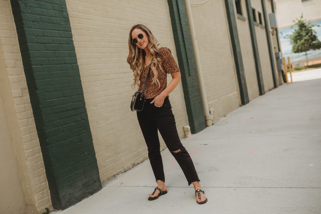 Shannon Jenkins of upbeatsoles styles a casual summer outfit with a leopard crop top and distressed black levi jeans with Ash sandals