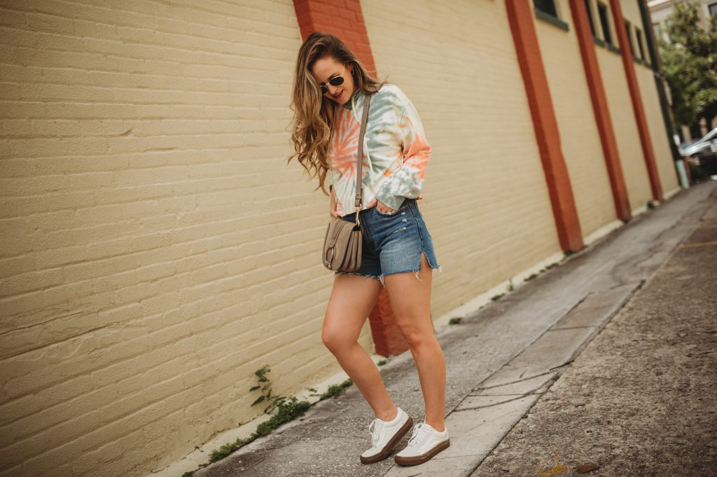 Shannon of Upbeat Soles styles a tie dyed crop hoodie with distressed denim shorts and vans