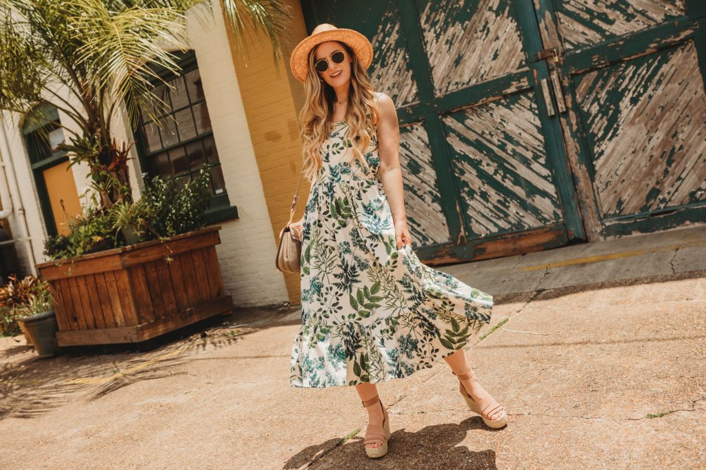 Shannon Jenkins of Upbeat Soles styles a cute vacation outfit with palm and leaves print midi dress from Chicwish, Dolce Vita wedges, and straw hat
