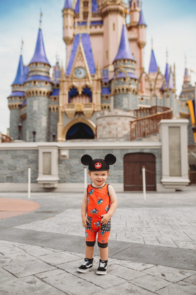 Shannon Jenkins of Upbeat Soles takes Disney 1 year old photos in front of the Magic Kingdom Castle styled in Disney Rags and toddler Vans