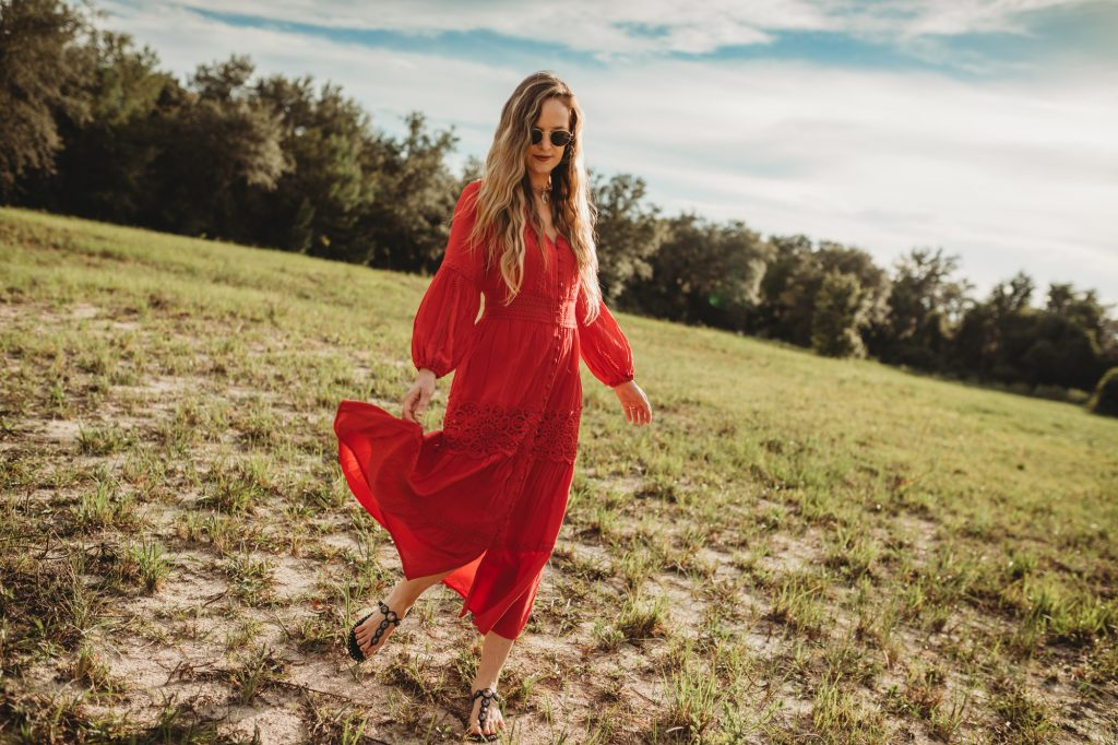 Shannon Jenkins of Upbeat Soles styles a boho maxi dress outfit with Chicwish red maxi dress, Ash sandals, and round Ray Bans