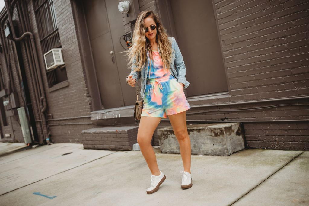 Shannon Jenkins of Upbeat Soles styles cute lounge wear with tie dye set, white Vans, and round Ray Ban sunglasses