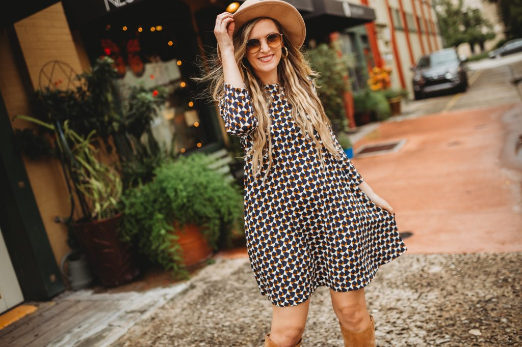 Shannon Jenkins of Upbeat Soles styles a cute fall transition outfit with a geometric dress, slouchy suede boots, and felt hat