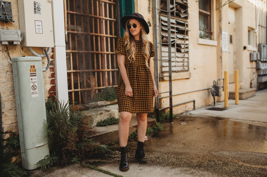 Shannon Jenkins of Upbeat Soles styles an edgy fall outfit with Target gingham dress, Dr Martens boots, and black woven hat