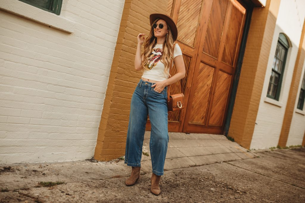 Shannon Jenkins of Upbeat Soles styles a fall boho outfit with tie dye Rolling stones tee, wide leg cropped jeans, and suede ankle booties