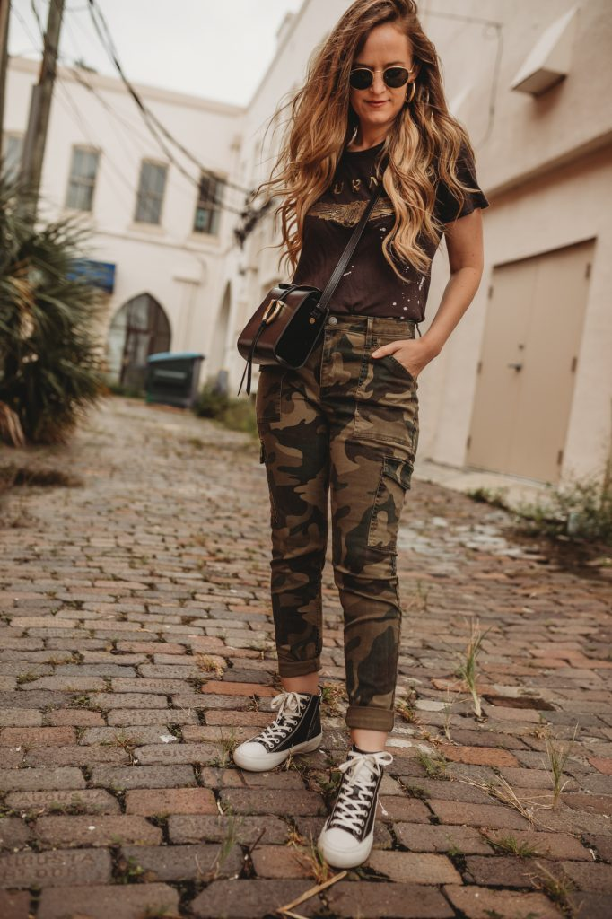 Shannon Jenkins of Upbeat Soles styles a casual fall outfit with band tee, camo jeans, and high top sneakers