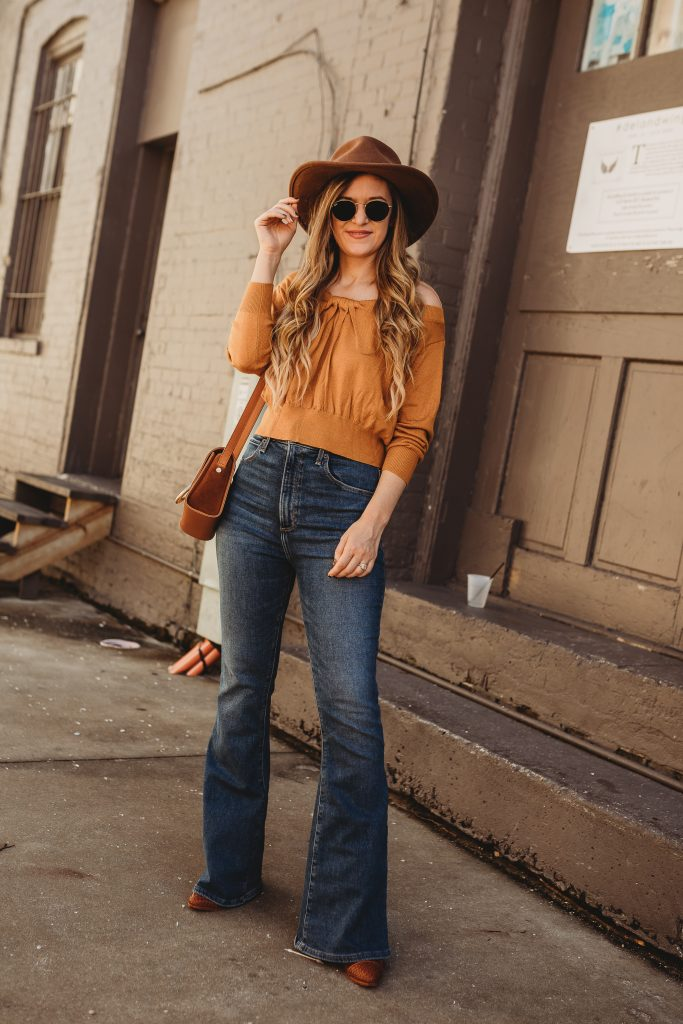 Shannon Jenkins of Upbeat Soles styles a boho winter outfit with mustard off the shoulder sweater, Abercrombie flare jeans, and Sancia bag