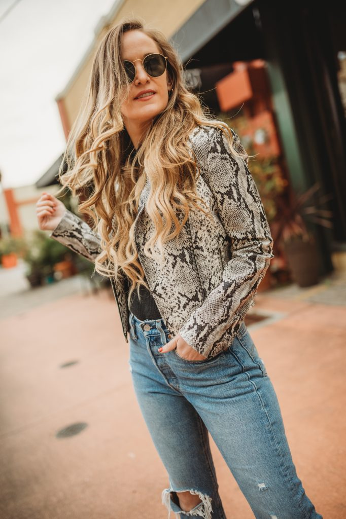 Shannon Jenkins of Upbeat Soles styles an edgy winter outfit styles with a snakeskin moto jacket, Levi's and black ankle booties