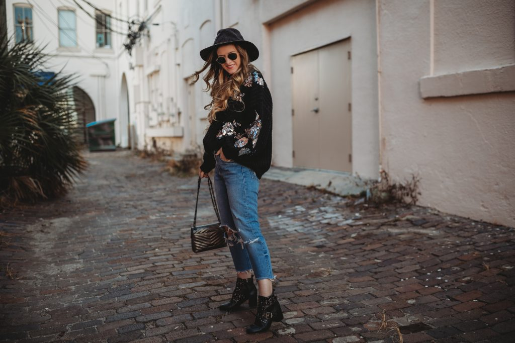 Shannon Jenkins of Upbeat Soles styles an edgy winter outfit with sequin black sweater, Levi's jeans, and black studded booties
