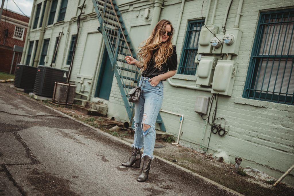 Shannon Jenkins of Upbeat Soles styles an edgy date night outfit with Leather shirt, mom jeans, and metallic booties