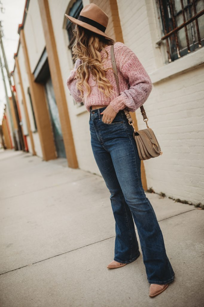 Shannon Jenkins of Upbeat Soles styles a flared jeans winter outfit with cropped sweater, high waisted flared jeans, and wool hat