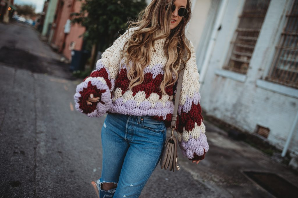 Shannon Jenkins of Upbeat Soles styles a boho winter outfit with oversized Chicwish sweater, Levi's mom jeans, and caged booties