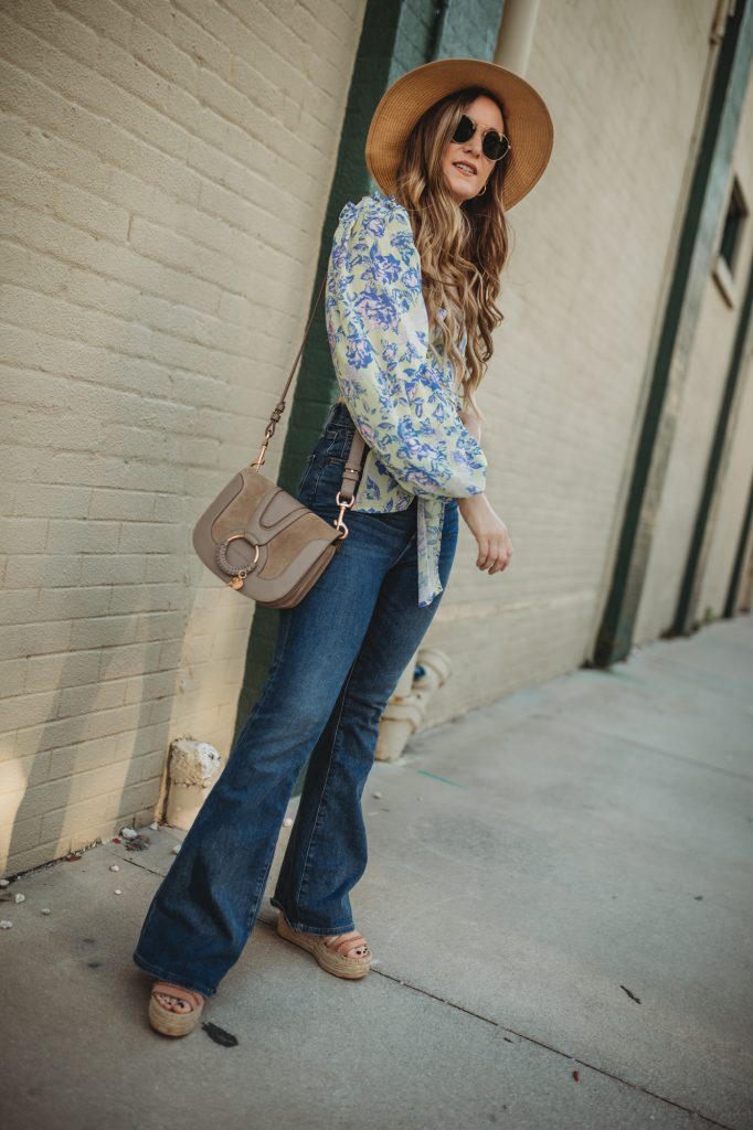 Shannon Jenkins of Upbeat Soles styles a cute spring weekend outfit with wrap crop top, high waisted flared jeans, and wedges