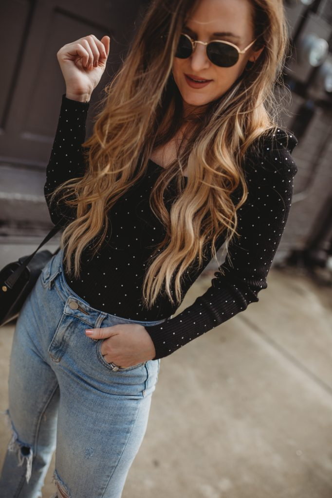 Shannon Jenkins of Upbeat Soles styles an edgy date night outfit with studded sweater, mom jeans, and studded booties