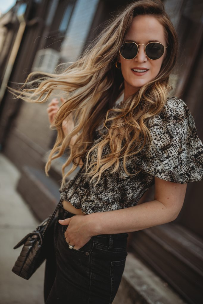 Shannon Jenkins of Upbeat Soles styles a spring transition outfit with Free People snakeskin crop top and black flared jeans