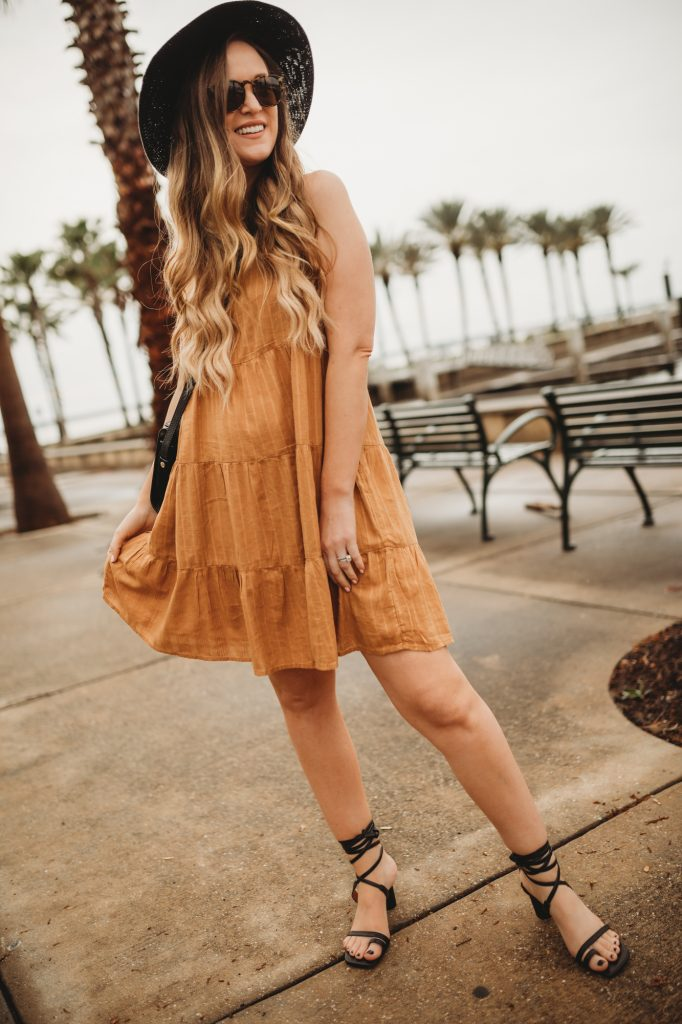 Shannon Jenkins of Upbeat Soles styles a spring boho outfit with mustard Old Navy dress, lace up sandals, and black fedora
