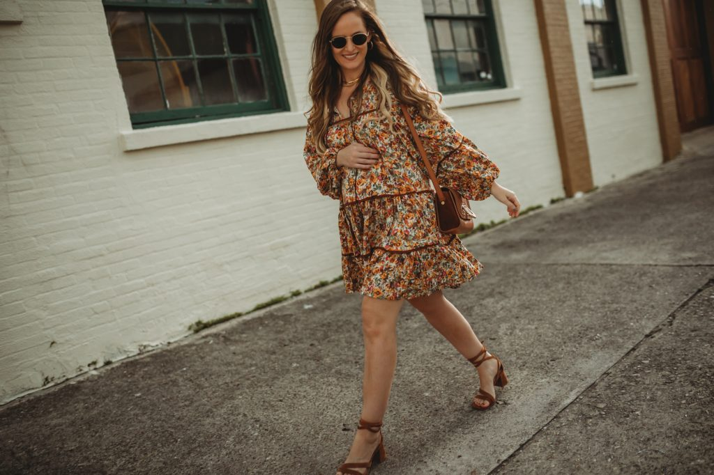 Shannon Jenkins of Upbeat Soles styles a boho maternity outfit with Chicwish dark floral boho dress, lace up sandals, and Sancia Bag