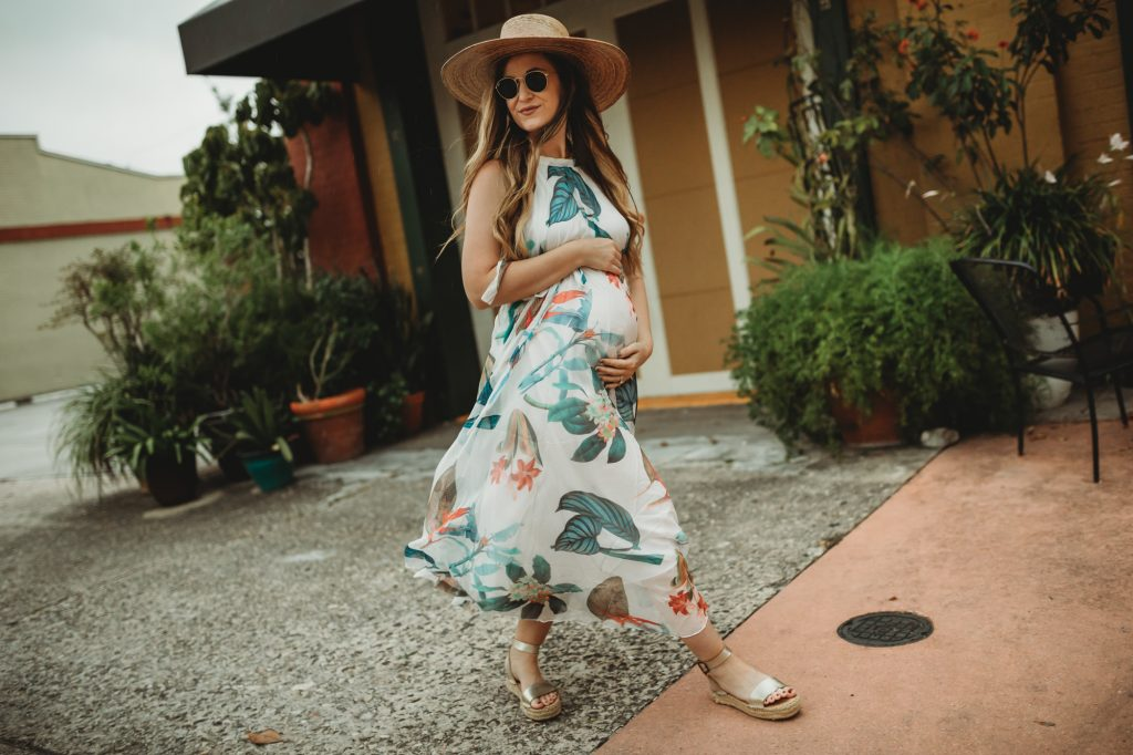 Shannon Jenkins of Upbeat Soles styles maternity vacation outfit with tropical maxi Chicwish dress, metallic sandals, and Lack of Color hat