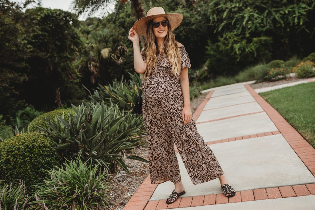 Shannon Jenkins of Upbeat Soles styles a stylish maternity outfit with leopard maternity jumpsuit, studded sandals, and straw sun hat